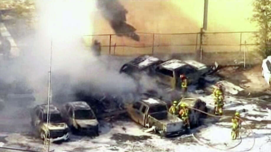 In this image taken from video, first responders work to extinguish burning vehicles after a small plane crashed into a parking lot near Fort Lauderdale Executive Airport in Fort Lauderdale, Fla. Friday afternoon killing all three people on board and burning about a dozen cars. No one on the ground was hurt. Photo: AP