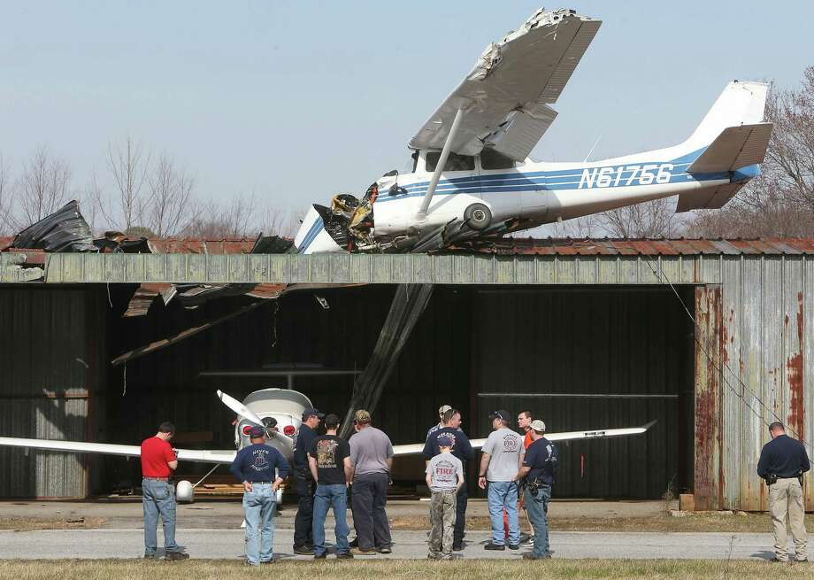 Fire and law enforcement personal look over a plane that crashed on top of a hangar at the Hendersonville Airport in Hendersonville, N.C., on Friday. The pilot, Andrew Michael Bell, 35, of Zirconia, N.C., suffered only minor injuries. No one else was aboard the plane. The crash did not suspend operations at the Hendersonville Airport, which remained open for air traffic. The National Transportation Safety Board is investigating the crash. Photo: AP