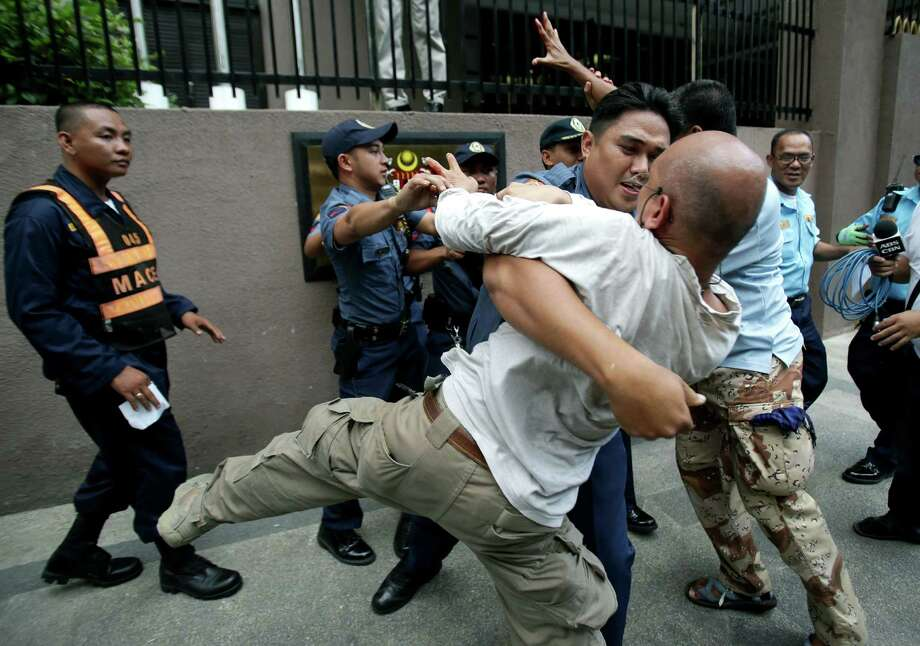A Filipino policeman prevents activists from touching a sign of the Malaysian Embassy during a rally to call for peace in Sabah at the financial district of Makati, south of Manila, Philippines on Thursday. Malaysian authorities will not let armed members of a Filipino royal clan who are being hunted in Borneo meet with Philippine officials or family members who might seek to negotiate their safety, the Malaysian foreign minister recently said. Photo: AP