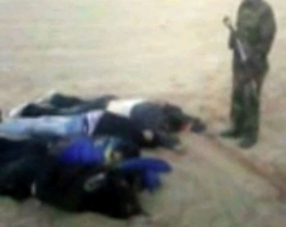 In this image from video posted on an Islamist web site, an armed man appears to stand over the what are claimed to be the corpses of some of the seven foreign hostages abducted from northern Nigeria and later killed by Islamic extremists. European diplomats confirmed Sunday that the hostages from Greece, Italy, Lebanon and Britain had been killed after their abduction Feb. 16. Nigerian authorities have been silent about the killings. Photo: AP