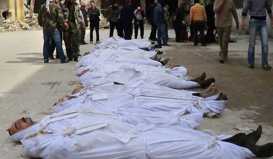 This citizen journalism image taken on Sunday and provided by Aleppo Media Center AMC which has been authenticated based on its contents and other AP reporting, shows Syrians standing next to dead bodies that have been pulled from the river near Aleppo's Bustan al-Qasr neighborhood, Syria. Activists said the dead bodies of at least 20 men were pulled from a river that runs between regime- and rebel-controlled parts of the northern city. Photo: AP