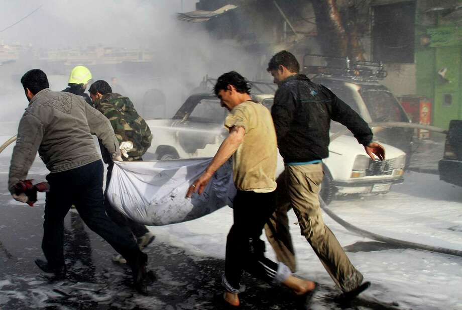 In this photo released by the Syrian official news agency SANA, Syrian citizens carry a dead body, at the scene where two mortar rounds exploded near an orphanage, at al-Boukhtyar area, in Damascus, Syria, on Wednesday. The state-run SANA news agency said two mortar rounds exploded near an orphanage in al-Boukhtyar area, killing and wounding an unknown number of people. Syrian government troops fought fierce battles with rebels on Wednesday for control of key neighborhoods in the north of Damascus, residents and activists said. Photo: AP