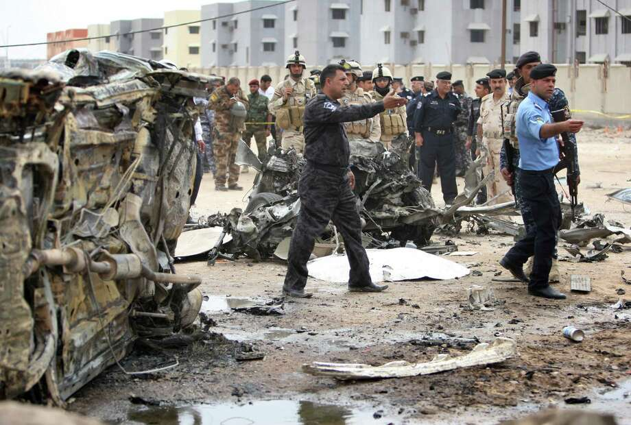 Iraqi security forces stand at the site of a car bomb attack in Basra, Iraq, Sunday, March 17, 2013. Iraqi authorities say two car bombs have killed several people and wounded scores of others in the country's south. Two police officials said that the first blast took place near a parking lot near the Tax Department in the centre of Basra. Fifteen minutes later, a second bomb went off near an outdoor market in another part of the oil-rich city. Photo: AP