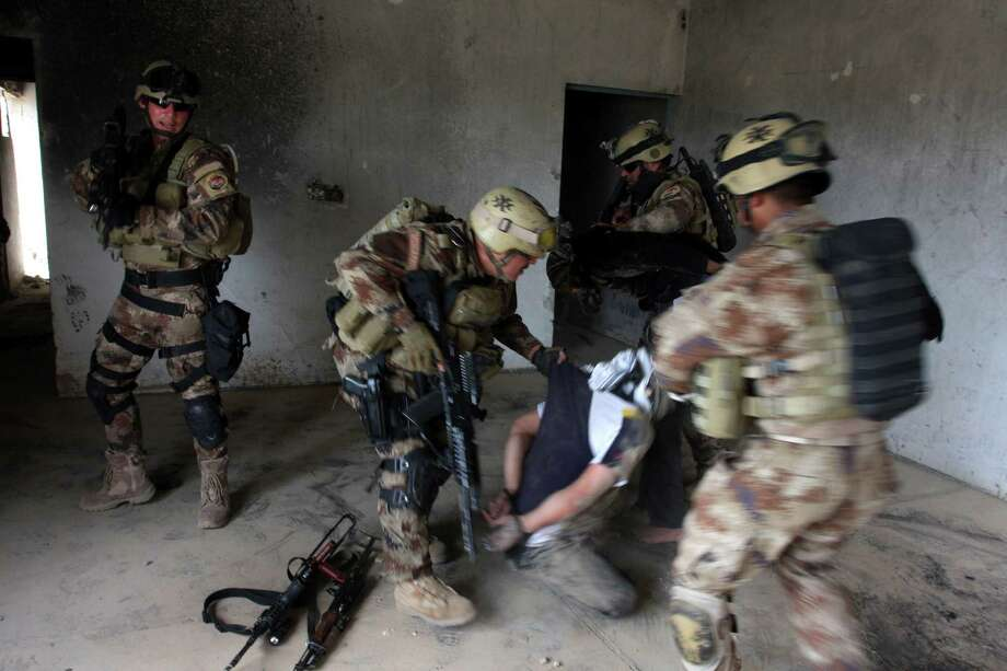 A suspected al-Qaida member is detained in an Iraqi SWAT raid in Latifiyah, Iraq, on Saturday.  Photo: AP