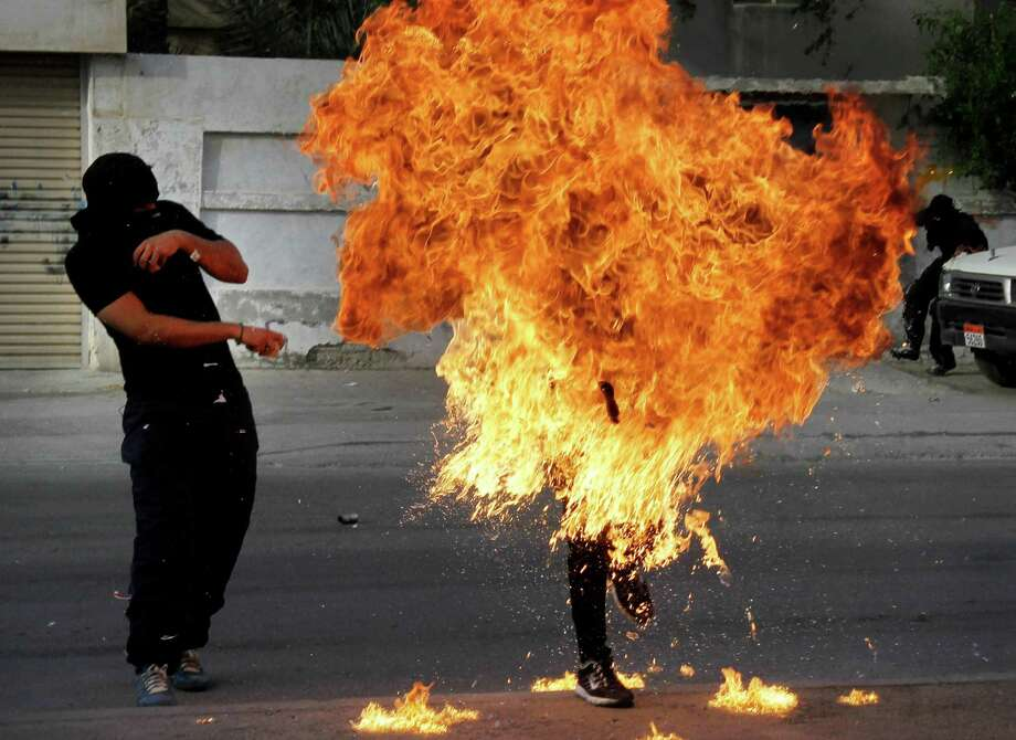 """A Bahraini anti-government protester is engulfed in flames when a shot fired by riot police hit the petrol bomb in his hand that he was preparing to throw during clashes in Sanabis, Bahrain, Thursday. Protests and clashes erupted in opposition areas nationwide Thursday with government opponents observing a """"Dignity Strike"""" blocking roads, closing shops, protesting and staying home from work and school called by the more radical February 14 youth group. Photo: AP"""