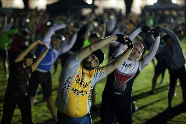 John Rigby takes part in a pre-ride group stretch at Tour de Houston, March 17, 2013 in Houston. Photo: Eric Kayne, For The Chronicle / © 2013 Eric Kayne