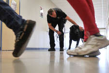 As students exit a classroom. officer Jeff Hastings of the Granbury Police Department waits with his dog Ben, to do a drug search of that classroom at Somerset Junior High School.