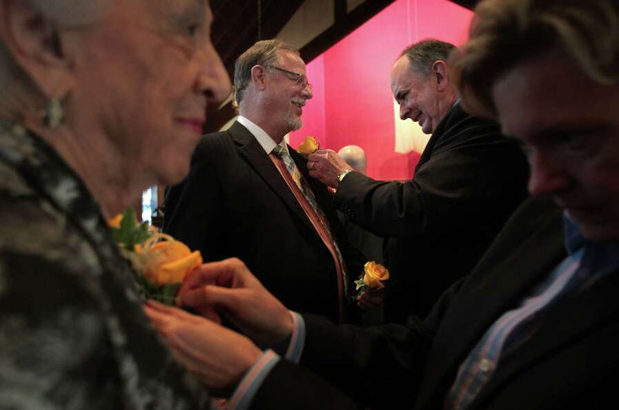 Jeff Meadows smiles as partner Gary Patterson pins his boutonniere before their ceremony, The Witnes