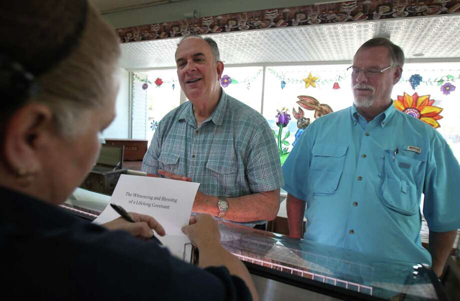 """The Witnessing and Blessing of a Lifelong Covenant Jeff & Gary, John 15: 9-12"" instructs Gary Patterson to be written on their cake as partner Jeff Meadows looks on at Moeller's Bakery on Monday, March 11, 2013, in Houston. Patterson and Meadows will be the first couple to participate in the Lifelong Commitment ceremony in Houston after the national church wrote the blessing in the summer of 2012. The Bishop of the Diocese of Texas granted St. Stephen's the opportunity to offer the blessing. Photo: Mayra Beltran, Houston Chronicle / © 2013 Houston Chronicle"