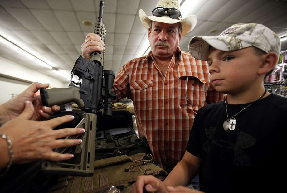 Johnny Hickman and son Jake, 10, of Midland listen to Connie Whiting of Five Four Tactical explain how an AR-15 has been customized at the Sweetwater Gun, Knife and Coin Show in Odessa on Saturday. Photo: Edyta Blaszczyk, Associated Press / Odessa American