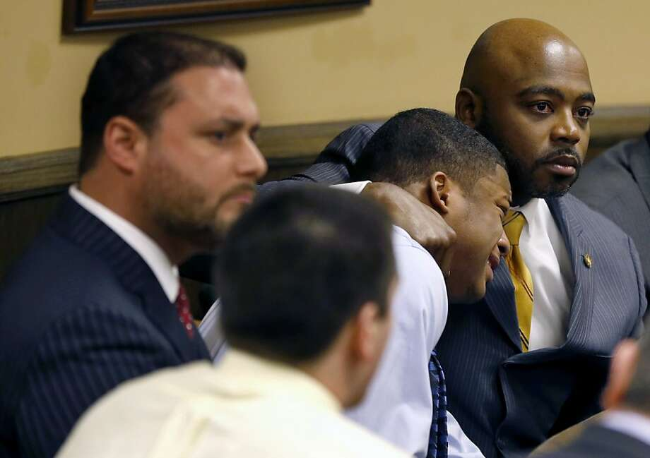 Defense attorney Walter Madison, right, holds his client, 16-year-old Ma'lik Richmond, second from right, while defense attorney Adam Nemann, left, sits with his client Trent Mays, foreground, 17, as Judge Thomas Lipps pronounces them both delinquent on rape and other charges after their trial in juvenile court in Steubenville, Ohio, Sunday, March 17, 2013. Mays and Richmond were accused of raping a 16-year-old West Virginia girl in August 2012.  Photo: Keith Srakocic, Associated Press