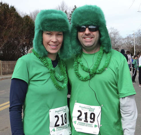 Jennifer and Matt DeLawder of Trumbull keep warm with fuzzy green hats near the start of the St. Patrick's Day 4-Mile Road Race on Sunday at Jennings Beach.  FAIRFIELD CITIZEN, CT 3/17/13 Photo: Mike Lauterborn