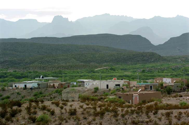 The Big Bend National Park's Chisos Mountains range rises behind Boquillas del Carmen, Mexico on Wednesday, July 21, 2004. ( JERRY LARA STAFF )