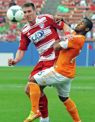 FC Dallas' Kenny Cooper (33) and Houston Dynamo's Corey Ashe (26) battle for the ball during an MLS soccer match, Sunday, March 17, 2013, in Frisco, Texas. FC Dallas won 3-2. (AP Photo/The Dallas Morning News, Mark M. Hancock) MANDATORY CREDIT; MAGS OUT; TV OUT; INTERNET OUT; AP MEMBERS ONLY Photo: Mark M. Hancock, Associated Press / The Dallas Morning News