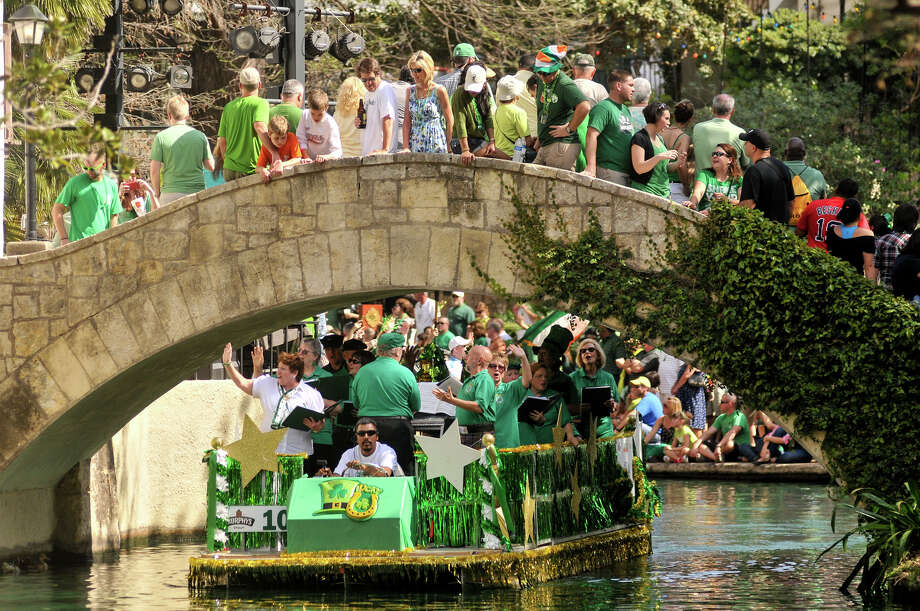 A parade barge passes under the Arneson River Theater bridge on the dyed-green San Antonio River during the annual St. Patrick's Day Parade Sunday afternoon, March 17, 2013. Photo: Robin Jerstad, For The San Antonio Express-News