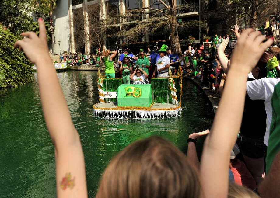 Cheers go up as the annual St. Patrick's Day Parade makes its way along the dyed-green San Antonio River Sunday afternoon, March 17, 2013. Photo: Robin Jerstad, For The San Antonio Express-News