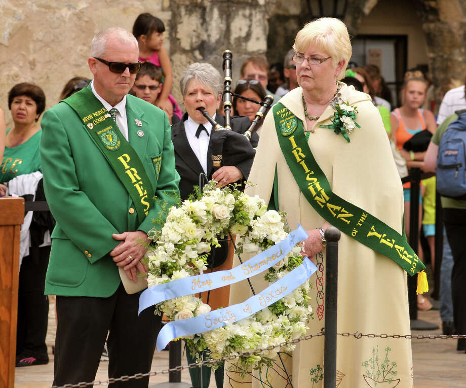 "Harp and Shamrock Society of Texas President Kevin Dowd and Irishman of the Year Mary Jo Quinn stand solemly with a wreath to honor the Irishmen who died at the Alamo as ""Amazing Grace"" is played during a ceremony at the Alamo Sunday, March 17, 2013. Photo: Robin Jerstad, For The San Antonio Express-News"