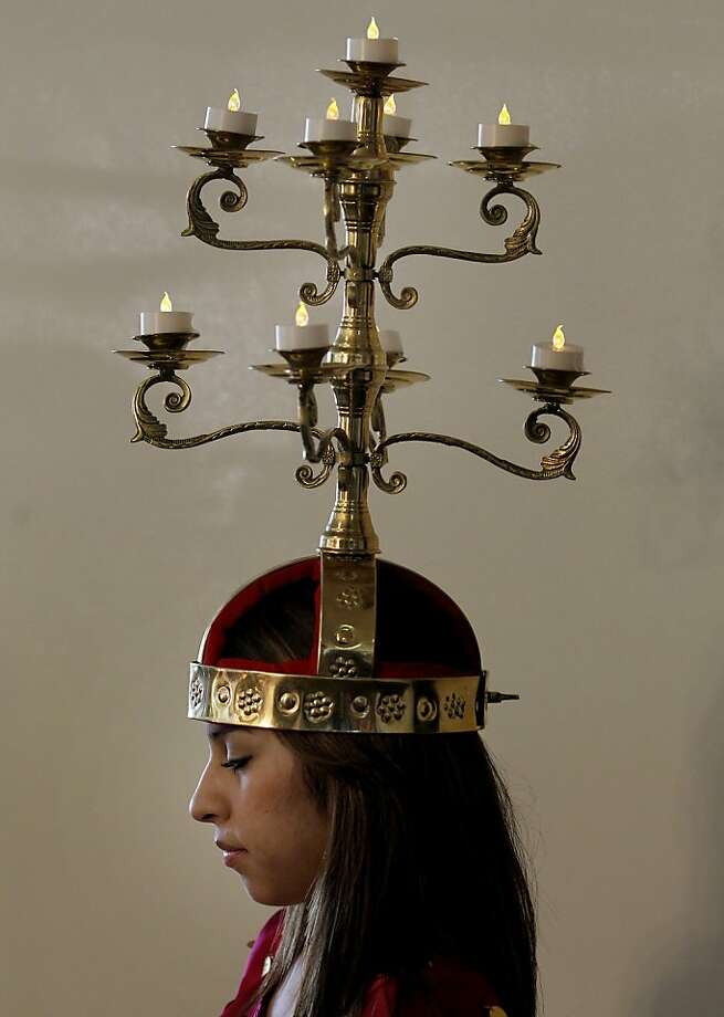 At right, Maria Segoviano balances a headpiece before she performs. Photo: Brant Ward, The Chronicle