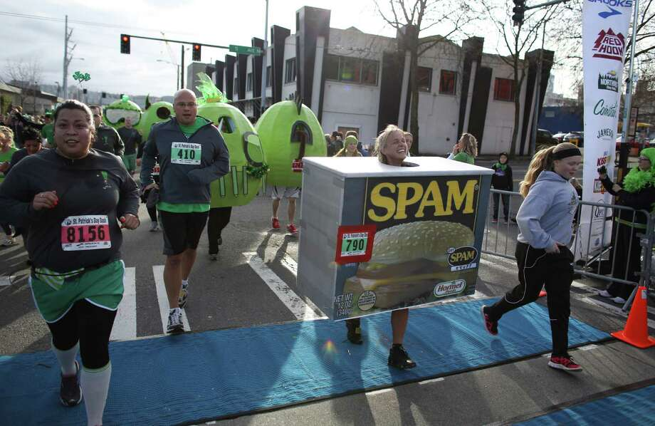 "People cross the finish line, including runners dressed as ""green eggs and Spam,"" during the St. Patrick's Day Dash in downtown Seattle. Thousands of green-clad people participated in the annual race and  beer fest at Seattle Center. Photo: JOSHUA TRUJILLO, SEATTLEPI.COM / SEATTLEPI.COM"