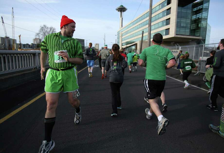 Kevin Koski of Bremerton runs the entire race backwards during the St. Patrick's Day Dash in downtown Seattle. This is his eight time running the race, backwards. Thousands of green-clad people participated in the annual race and  beer fest at Seattle Center. Photo: JOSHUA TRUJILLO, SEATTLEPI.COM / SEATTLEPI.COM