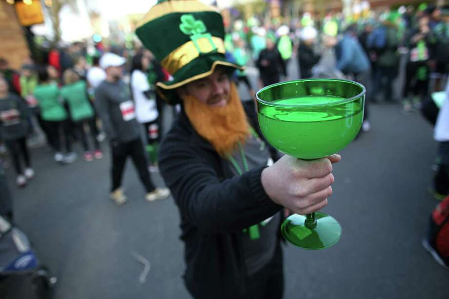 A participant hoists a glass of sports drink before running the St. Patrick's Day Dash in downtown Seattle. Thousands of green-clad people participated in the annual race and  beer fest at Seattle Center. Photo: JOSHUA TRUJILLO, SEATTLEPI.COM / SEATTLEPI.COM
