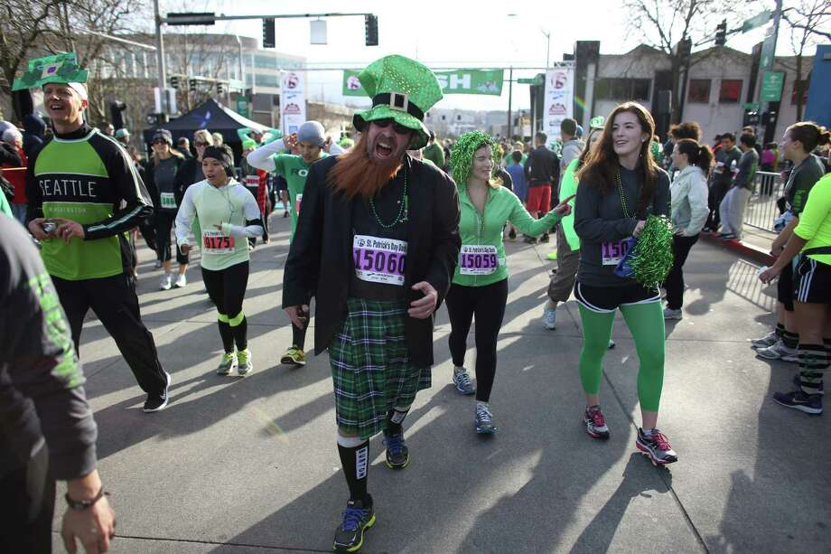 People cross the finish line during the St. Patrick's Day Dash in downtown Seattle. Thousands of green-clad people participated in the annual race and  beer fest at Seattle Center. Photo: JOSHUA TRUJILLO, SEATTLEPI.COM / SEATTLEPI.COM