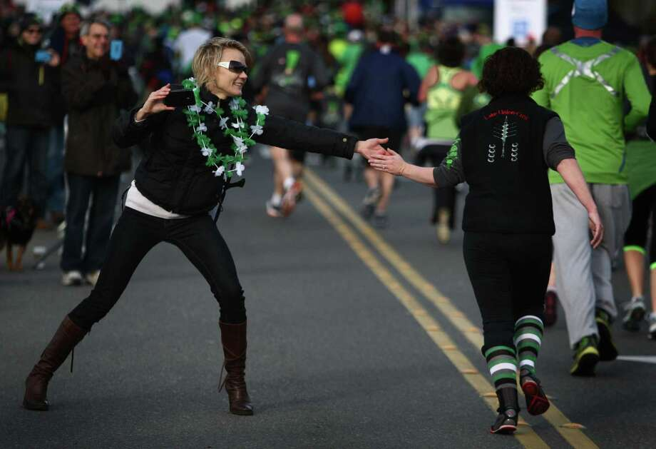 People are encouraged near the finish line during the St. Patrick's Day Dash in downtown Seattle. Thousands of green-clad people participated in the annual race and  beer fest at Seattle Center. Photo: JOSHUA TRUJILLO, SEATTLEPI.COM / SEATTLEPI.COM