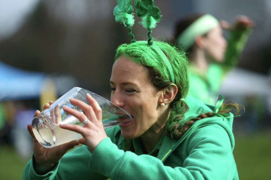 Female race winner Rose Wetzel takes a drink from her first place trophy after completing the St. Patrick's Day Dash in downtown Seattle. This is Wetzel's fourth time winning the annual race. Thousands of green-clad people participated in the annual race and  beer fest at Seattle Center. Photo: JOSHUA TRUJILLO, SEATTLEPI.COM / SEATTLEPI.COM