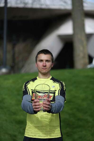 Male race winner Mike Sayenko holds his trophy after winning the St. Patrick's Day Dash in downtown