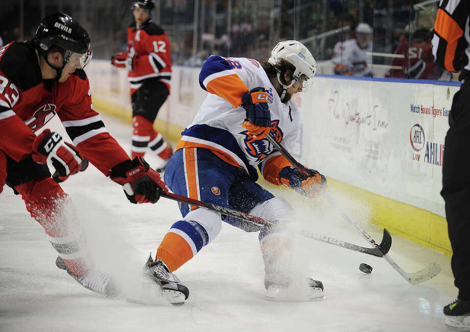 Albany's Corbin McPherson, left, chases Sound Tiger Brandon DeFazio into the corner during the second period of their AHL hockey matchup at Webster Bank Arena in Bridgeport, Conn. on Sunday, March 17, 2013. Photo: Brian A. Pounds / Connecticut Post