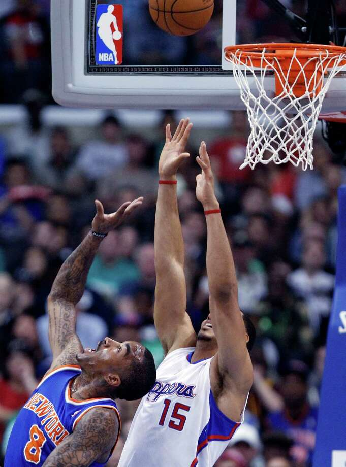 New York Knicks guard J.R. Smith (8) shoots as Los Angeles Clippers center Ryan Hollins (15) defends in the first half of an NBA basketball game in Los Angeles Sunday, March 17, 2013. (AP Photo/Reed Saxon) Photo: Reed Saxon