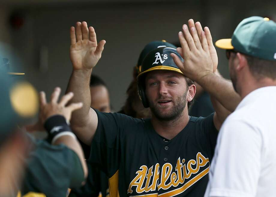 Oakland Athletics' Shane Peterson gets high-fives from teammates after he scores a run against the Arizona Diamondbacks during an MLB spring training baseball game on Friday, March 15, 2013, in Scottsdale, Ariz.  The game ended in a 2-2 tie. (AP Photo/Ross D. Franklin) Photo: Ross D. Franklin, Associated Press