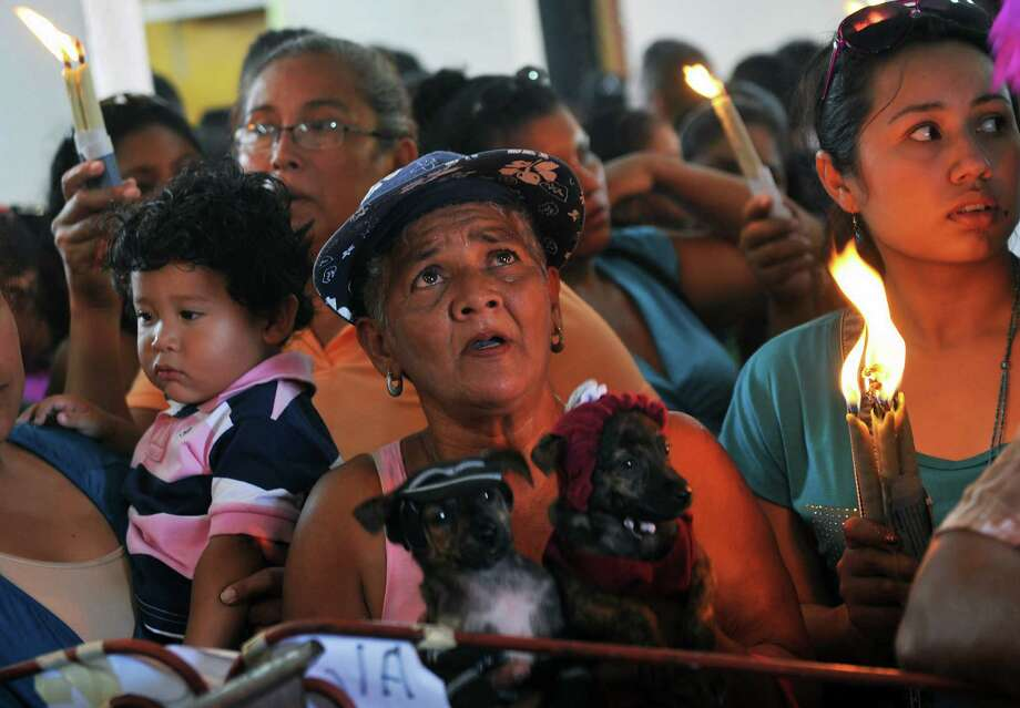 A woman holds their dressed dogs during a mass for San Lazaro, on March 17, 2013, in the neighborhood Monimbo in Masaya, 30 km south of Managua. According to tradition in Nicaragua, faithfuls ask for the health of their dogs at San Lazaro and they pay these favors back bringing them dressed in costumes to attend mass in honor of the saint. Photo: HECTOR RETAMAL, AFP/Getty Images / AFP