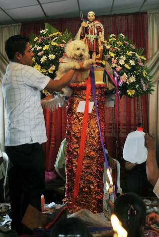 A parishioner holds a dog in front of the image of San Lazaro, during a mass in his honor, on March 17, 2013, in Monimbo neighborhood, in Masaya, 30km south of Managua. According to tradition in Nicaragua, faithfuls ask for the health of their dogs at San Lazaro and they pay these favors back bringing them dressed in costumes to attend mass in honor of the saint. Photo: HECTOR RETAMAL, AFP/Getty Images / AFP