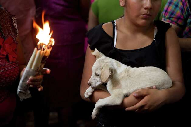 A woman holds her dog during an animal blessing ceremony in honor of Saint Lazarus, patron of the sick, at a church in the Monimbo neighborhood of Masaya, Nicaragua, Sunday, March, 17, 2013. Catholics in Nicaragua associated Saint Lazarus with dogs, and dress up their pets for a Catholic blessing, asking the saint to keep their dogs healthy. Photo: Esteban Felix, Associated Press / AP