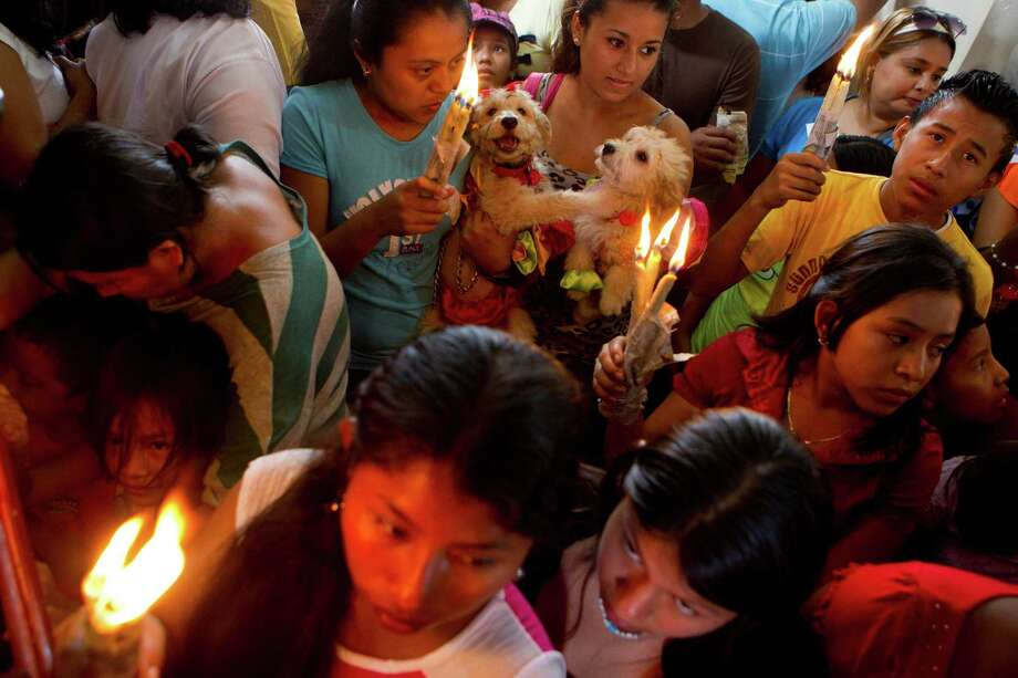 Women carry their dogs wearing costumes in honor of Saint Lazarus, patron of the sick, at a church in the Monimbo neighborhood of Masaya, Nicaragua, Sunday, March, 17, 2013. Catholics in Nicaragua associated Saint Lazarus with dogs, and dress up their pets before a Catholic blessing, asking the saint to keep their dogs healthy. Photo: Esteban Felix, Associated Press / AP