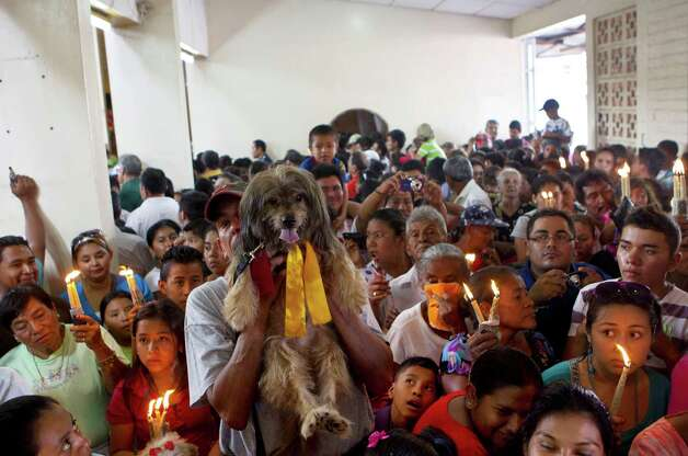 A man holds up his dog during an animal blessing ceremony in honor of Saint Lazarus, patron of the sick, at a church in the Monimbo neighborhood of Masaya, Nicaragua, Sunday, March, 17, 2013. Catholics in Nicaragua associated Saint Lazarus with dogs, and dress up their pets for a Catholic blessing, asking the saint to keep their dogs healthy. Photo: Esteban Felix, Associated Press / AP