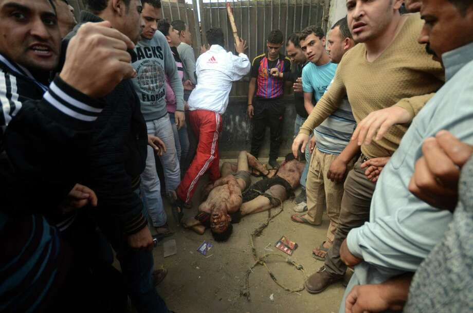 EDS NOTE GRAPHIC CONTENT -- Egyptian men surround the bodies of two men who were beaten and hung by vigilantes after being accused of theft in Samanod, about 55 miles (90 kilometers) north of Cairo, Egypt, Sunday March 17, 2013. Egyptian vigilantes beat two men accused of stealing a motorized rickshaw, then stripped them half-naked and hung them still alive in a bus station in a small Nile Delta town on Sunday, according to security officials who said both men died. The killings came a week after the attorney general's office encouraged civilians to arrest lawbreakers and hand them over to police. (AP Photo) Photo: Uncredited