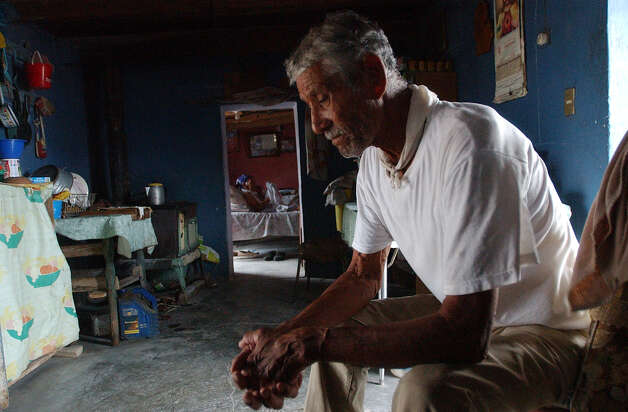 Pablo Robles Luna, 78, sits in his home as his wife, Reyna, 90, folds clothing on the bed in Boquillas del Carmen, Mexico on Wednesday, July 21, 2004. Robles used to sell rocks and handmade gifts to tourists who would cross the Rio Grande from Big Bend National Park. That came to a stop when the federal government stop the crossings after the Sept. 11 attacks. Photo: JERRY LARA, San Antonio Express-News / SAN ANTONIO EXPRESS-NEWS