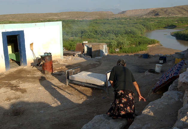 Cruz Gonzalez Vasquez, 66, makes her way down a rocky path to tend her stove, the barrel in the background, in Boquillas del Carmen, Mexico, on Thursday, July 22, 2004. In sight of the Rio Grande, she relied on tourists from the U.S. for the family's income. The crossing was shut down in May 2002 in reaction to the Sept. 11 attacks. Photo: JERRY LARA, San Antonio Express-News / SAN ANTONIO EXPRESS-NEWS