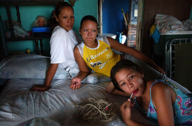 Elvia Martinez Ureste, 25, left, sits with her cousins, Yadira Diaz Padilla, 13, center, and Judith Diaz Padilla, 10, in Boquillas del Carmen, Mexico on Wednesday, July 21, 2004. Teachers and doctors for the children have to travel over 160 miles to the town which is located across the Rio Grande from Big Bend National Park. Before the federal government closed off the access across the river in May 2002, residents relied heavily on the U.S. side for emergency medical services, food and tourists. Photo: JERRY LARA, San Antonio Express-News / SAN ANTONIO EXPRESS-NEWS