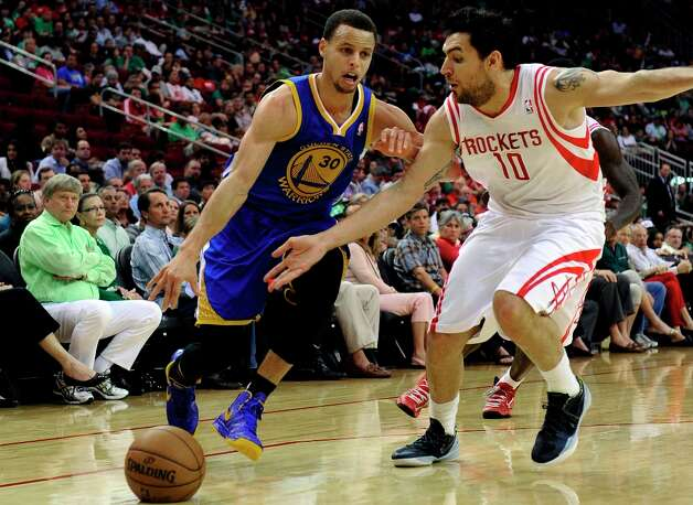 Warriors guard Stephen Curry drives the ball past Rockets forward Carlos Delfino (10) in the first half. Photo: Pat Sullivan