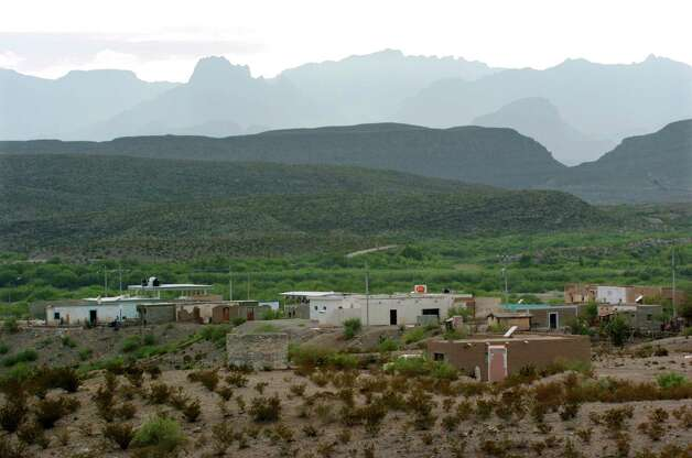 The Big Bend National Park's Chisos Mountains range rises behind Boquillas del Carmen, Mexico on Wednesday, July 21, 2004. A new automated U.S.-Mexico border port connecting the town to the park on the banks of the Rio Grande is quietly expected to open soon under an agreement between the neighboring countries. Photo: JERRY LARA, San Antonio Express-News / SAN ANTONIO EXPRESS-NEWS