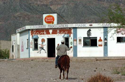 A rider makes his way past the Park Bar in Boquillas del Carmen, Mexico, on Wednesday, July 21, 2004. Once a popular spot for U.S. tourists from Big Bend National Park, the bar remains open after the border was shut down by the U.S. Federal government May 2002. Photo: JERRY LARA, San Antonio Express-News / SAN ANTONIO EXPRESS-NEWS