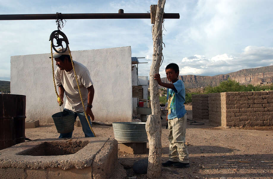 Guadalupe Davila, 56, draws water from a well in Boquillas del Carmen, Mexico on Wednesday, July 21, 2004. Although the town has a water tower built by the government, Davila uses the well because residents have to pitch in $5 dollars a month for gasoline to run the pump. The town' main source of income, American tourists crossing the Rio Grande from Big Bend National Park, stopped after the Federal government closed the border in May 2002 in response to the Sept. 11 attacks. Photo: JERRY LARA, San Antonio Express-News / SAN ANTONIO EXPRESS-NEWS
