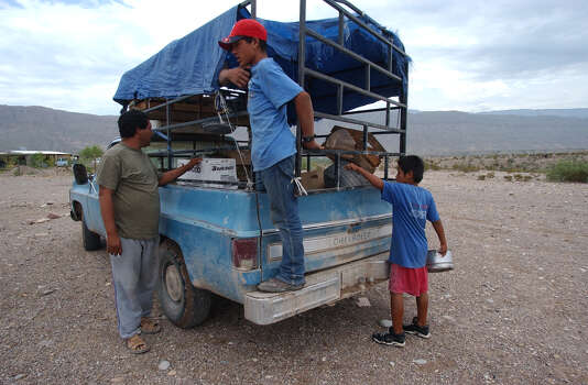 Ramon Cruz Alvarez, 36, left, sells produce in Boquillas del Carmen, Mexico on Wednesday, July 21, 2004. From the town of Ocampo, Coahuila, Cruz and worker, Francisco Manuel Carrera, 17, center, travel over 170 miles to isolated towns to sell their produce to residents like Adrian Martinez Ureste, 12, right, who bought tomatoes and hot dogs for his family. Once able to buy their food with American tourist dollars across the Rio Grande in Big Bend National Park, residents of Boquillas have to rely on traveling sales trucks since May 2002 when the federal government shut down border crossings in the area. Photo: JERRY LARA, San Antonio Express-News / SAN ANTONIO EXPRESS-NEWS