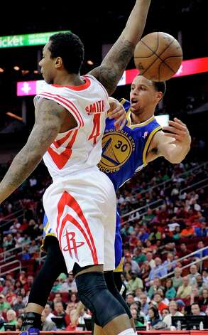 Warriors guard Stephen Curry passes the ball behind Rockets forward Greg Smith in the first half. Photo: Pat Sullivan