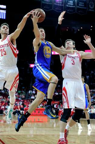Warriors guard Klay Thompson goes to the basket between Rockets forward Chandler Parsons (25) and center Omer Asik in the first half. Photo: Pat Sullivan