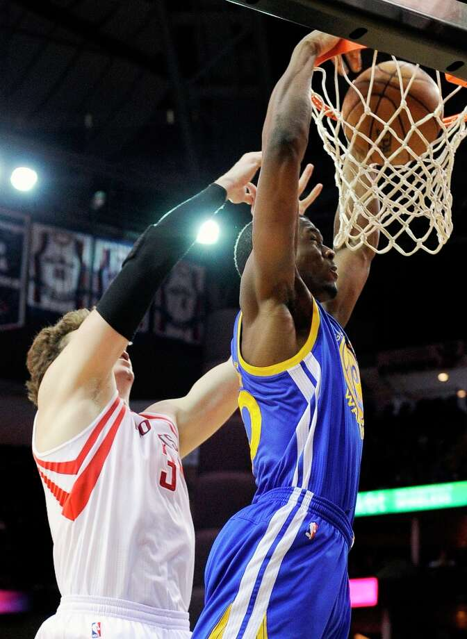 Harrison Barnes, right, dunks the ball in front of Rockets center Omer Asik in the first half. Photo: Pat Sullivan