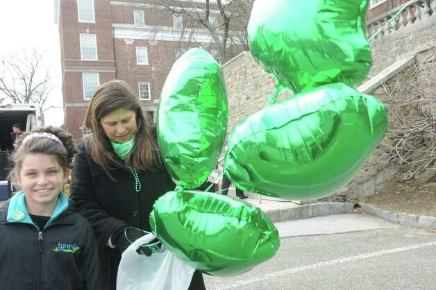 Morgan Felletter, 9, with her mother Brenda, brings green balloons at the Greenwich's 39th annual St. Patrick's Day parade at Greenwich Avenue, in Greenwich, Conn., March 17, 2013. Photo: Helen Neafsey / Greenwich Time